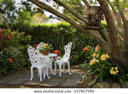 Garden furniture in a tranquil, lush garden setting - stock photo