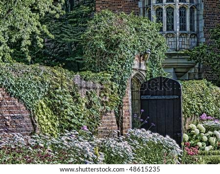 Garden gate stands open for entrance into the secret garden - stock photo
