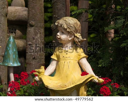 Garden gnome dwarf statue of a cute girl made from wood - stock photo