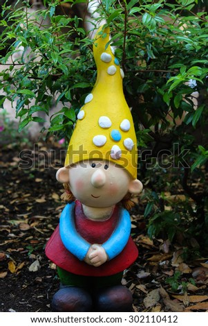 garden gnome female seems happy in his garden - stock photo