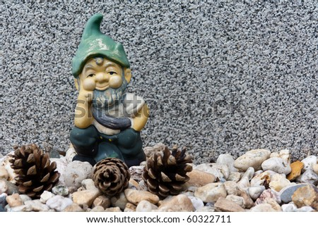 Garden Gnome on pebbles and pine cones - stock photo