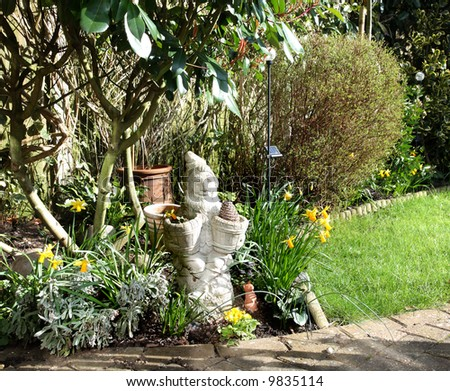 Garden Gnome Planter surrounded by Daffodils in an English Country Garden - stock photo