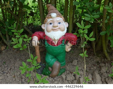 Garden Gnome with shovel at  work in front of a green hedge
