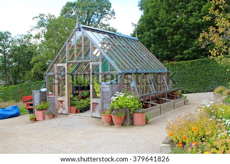 garden greenhouse with cold frame and pots - stock photo