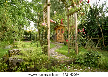 Garden idyll with a garden shed and rose arch with blooming red roses  - stock photo