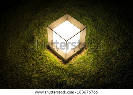 Garden lantern in shape of cube with dim light striking upon green lawn at night. Outdoor decoration and lighting. Warm and romantic atmosphere of evening. Illumination in garden or park. - stock photo