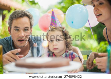 Garden party for daughter's birthday with mum and dad, The 3 years old birthday girl is pulling a face - stock photo