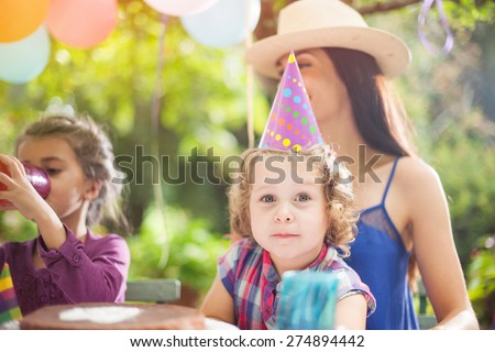 garden party with family for little girl's birthday, children blows out the candles on the cake, the garden is decorated with balloons and colors are bright  - stock photo