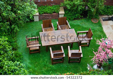 Garden patio with table and chairs after raining - stock photo
