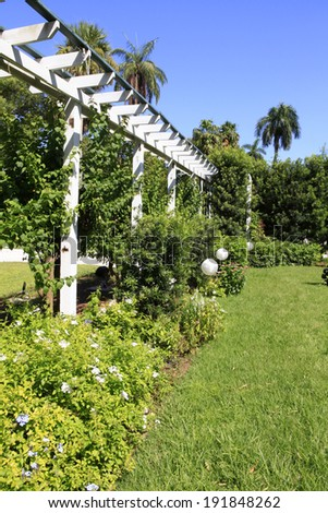 Garden pergola with trees and blooming bushes. Edison and Ford Museum. Florida.
