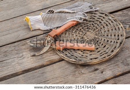 Garden pruner and gardening gloves on vintage wood board agriculture concept. - stock photo