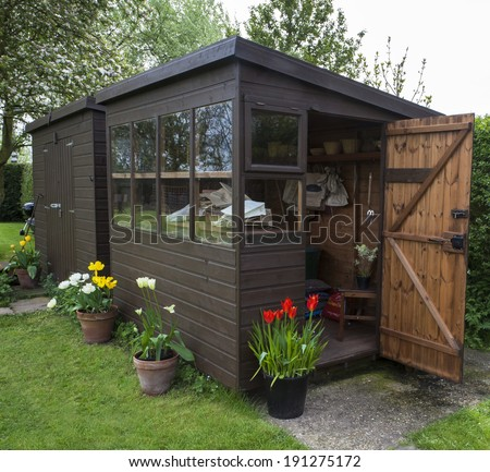 Garden shed exterior in Spring, with shed door open, lawn, tools, flowers, and plant pots. - stock photo