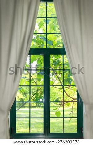 garden through the widow with curtains - stock photo