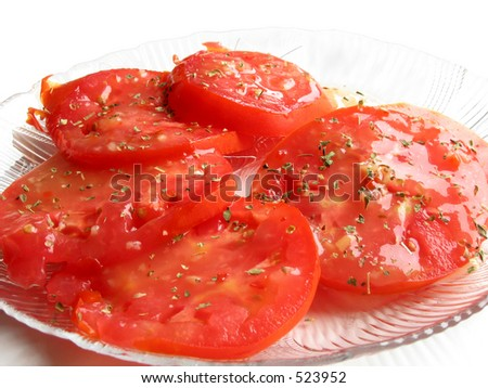 Garden tomatoes garnished with dressing and basil