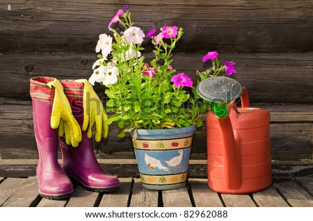 Garden tools (flower pot, watering can/ pot and rubber boots) horizontal image - stock photo