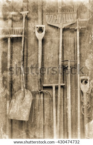 Garden tools hanging against a wooden wall, textured in sepia tones for a vintage lock.  - stock photo