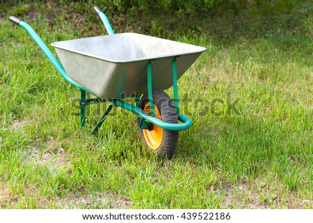 Garden tools on a green lawn. Wheelbarrow.