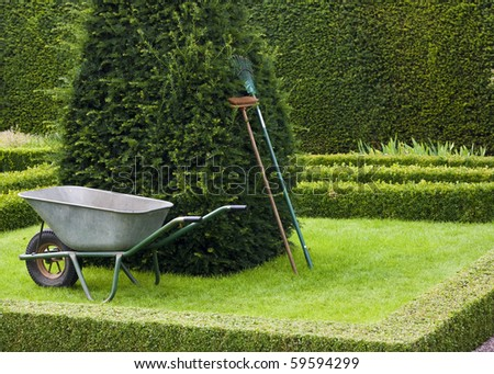 Garden tools placed neatly upright in a  tudor style knot garden with copy space. - stock photo