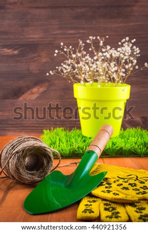 Garden tools, shovel, gloves, pot on a wooden table. Spring garden concept.