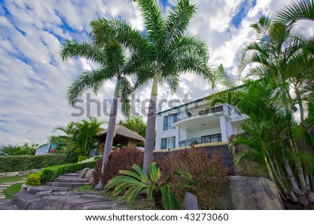 Garden with palms and Bali hut in front of waterfront mansion