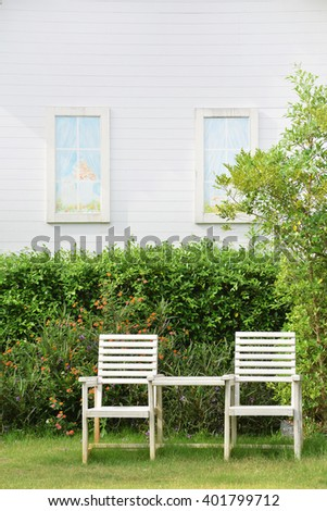 Garden with rustic white chair  with a white house wall background. - stock photo