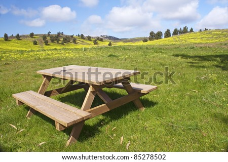 Garden wooden bench isolated in the green meadows - stock photo