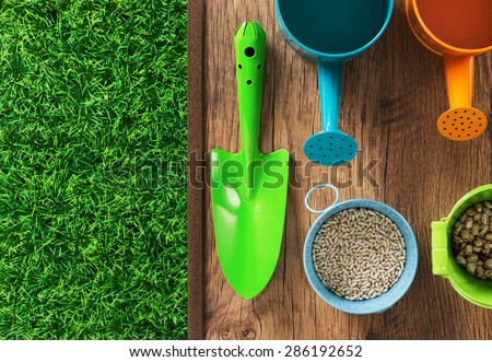 Gardener colorful work tools, seeds and green artificial turf on a wooden surface, top view - stock photo
