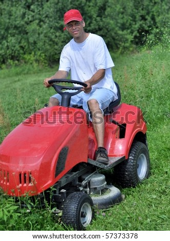 Gardener mowing the lawn - stock photo