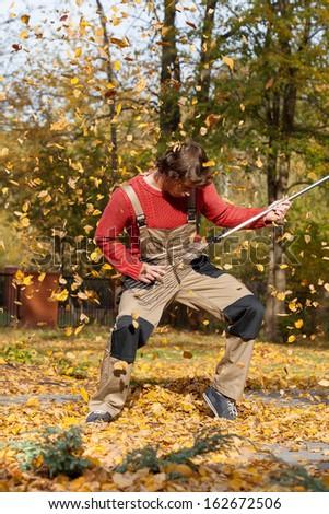 Gardener playing rock'n'roll during raking autumn leaves - stock photo