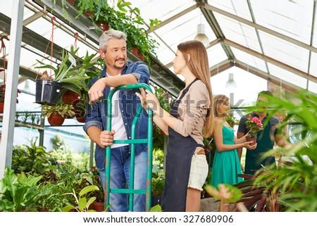 Gardener trainee in nursery shop talking with employee - stock photo