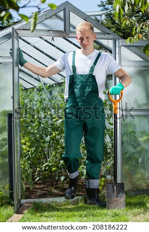 Gardener with a spade in front of greenhouse