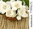 Gardenia in a wooden bowl on bamboo napkin bamboo - stock photo