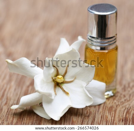 Gardenia or Gondhoraj flower with essence bottle on wooden surface - stock photo