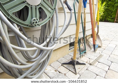 Gardening and Landscaping Tools and Equipment by Water Hose in Backyard - stock photo