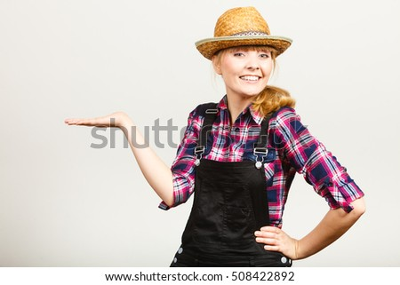Gardening concept. Attractive woman in dungarees, pink check shirt and sun hat showing something on her hand. Grey background