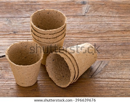 Gardening equipment. Peat biodegradable pots on wooden bench. - stock photo