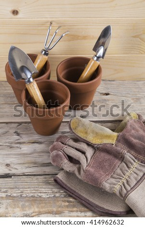 Gardening gloves with pots and tools - stock photo