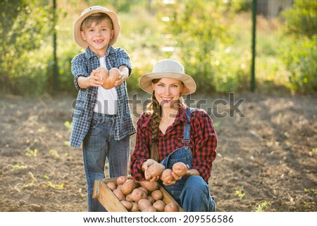 Gardening - happy mother with little son working in vegetable garden. focus on woman - stock photo