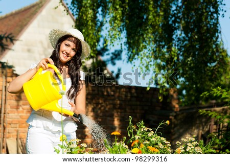 Gardening in summer - woman watering flowers with a yellow watering can, she is wearing a hat - stock photo