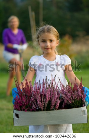 Gardening - lovely girl working with mother in the garden - stock photo