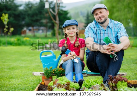 Gardening, planting, cultivation - young girl with father working in vegetable garden