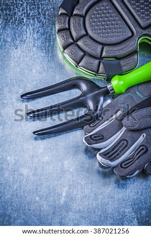 Gardening protective gloves knee pads trowel fork on metallic background agriculture concept. - stock photo