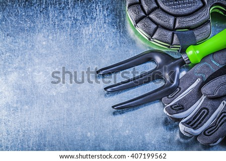 Gardening protective gloves knee protectors trowel fork on metallic background agriculture concept. - stock photo