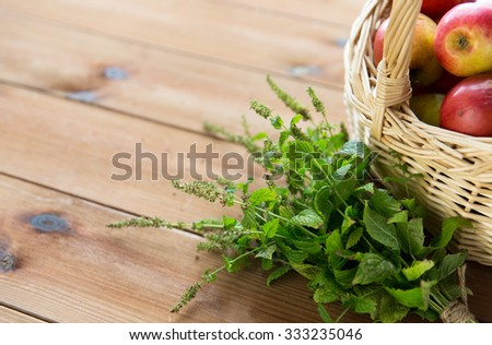 gardening, season, autumn, herbs and fruits concept - close up of wicker basket with ripe red apples and melissa bunch on wooden table - stock photo