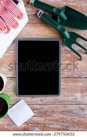 gardening, technology and planting concept - close up of tablet pc computer blank screen, seeds and garden tools on table - stock photo