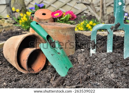 gardening tools in the ground and spring flowers background - stock photo