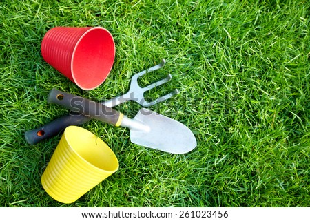 Gardening tools on green grass in the garden. - stock photo
