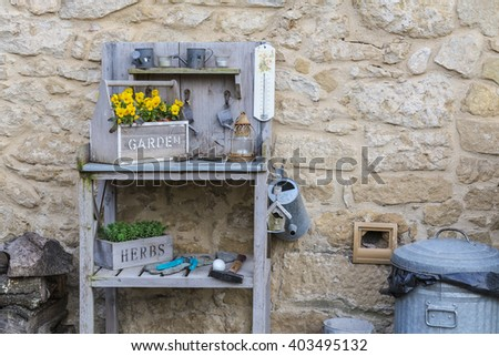 Gardening tools yellow flowers on a cobblestone wall