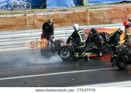 GARDERMOEN RACEWAY, NORWAY - MAY 14: Race driver Jan Birkenes crawls out of his burned out race car while fire fighters put out the fire on May 14,2011 at Gardermoen Raceway, Norway. - stock photo