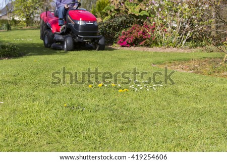 Gardner on ride on mowing the lawn green nature France - stock photo